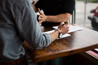 An image of two people talking over a table
